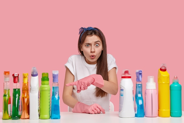 Zdjęcie zdziwionej młodej kobiety z okropnym wyrazem twarzy, wskazuje na butelki z detergentem, zszokowane jego cudownym efektem