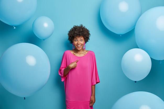 Zdjęcie zdziwionej wesołej kobiety wskazuje na siebie, nie może uwierzyć w sukces, coś świętuje, nosi różową sukienkę, stoi wokół balonu