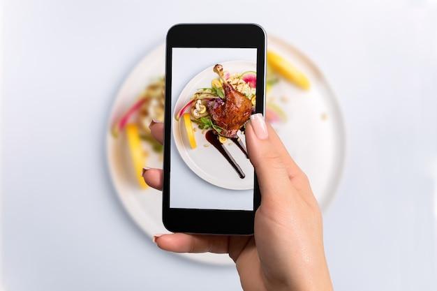Zdjęcie ze smartfona przedstawiające danie główne z udźca z kaczki i ustawienie świeżych warzyw