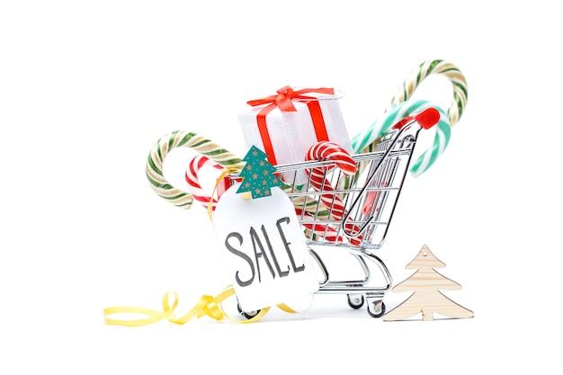 Zdjęcie żelaznego wózka z pudełkiem z prezentem, laski karmelu, karty na pustej bieli