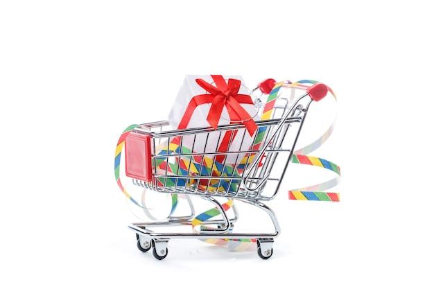 Zdjęcie żelaznego wózka z pudełkiem z prezentem, wstążkami na pustej białej powierzchni