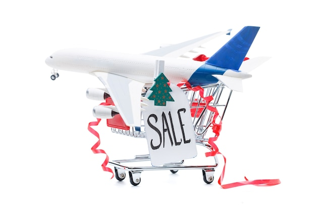 Zdjęcie żelaznego wózka z samolotem, pocztówkami, drewnianą choinką na pustej białej powierzchni