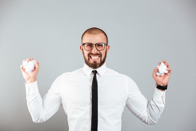 Zdjęcie zirytowany zły biznesmen w białej koszuli i okularach gnije dokumenty papierowe w obu rękach, odizolowane na szarej ścianie