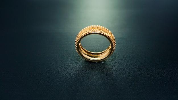 Zdjęcie złotego i błyszczącego pierścionka zaręczynowego