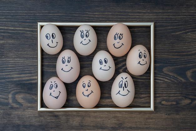 Zdjęcie złotej ramie i wiele zabawnych jaj uśmiechający się na tle ciemnej ściany drewniane, z bliska. portret twarz rodziny jaja. koncepcja śmieszne jedzenie