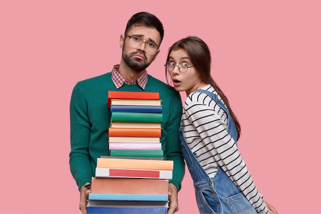 Zdjęcie zmęczonego, nieogolonego mężczyzny ze współczuciem, trzyma stos książek, patrzy z niezadowoleniem, jego koleżanka z klasy ma oszołomiony wygląd