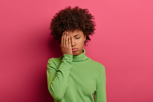 Zdjęcie zmęczonej afroamerykanki zakrywa dłonią połowę twarzy, ma zamknięte oczy, chce spać, potrzebuje odpoczynku