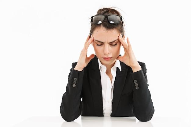 Zdjęcie zmęczonej pracownic kobieta ubrana w strój wizytowy dotykając jej głowy podczas pracy i siedząc przy biurku w biurze na białym tle nad białą ścianą