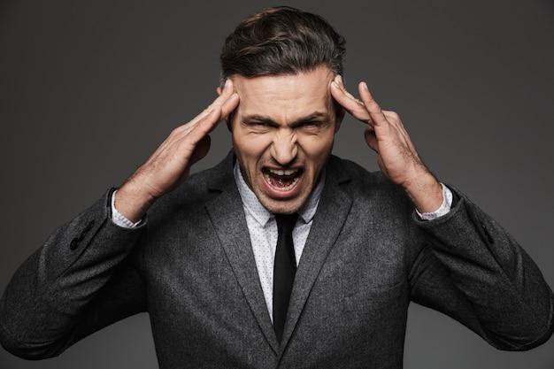 Zdjęcie zmęczony przepracowany biznesmen ubrany w formalny garnitur ściskając jego skronie i krzycząc, odizolowane na szarej ścianie