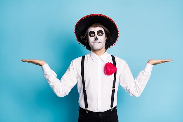 Zdjęcie zombie nieumarłych odgrywanie ról zabawny facet dzień śmierci nadruk twarzy makijaż trzymaj otwarte ramiona prezentując dwa produkty wybór nosić kapelusz kostium szelki koszula na białym tle niebieski kolor tła