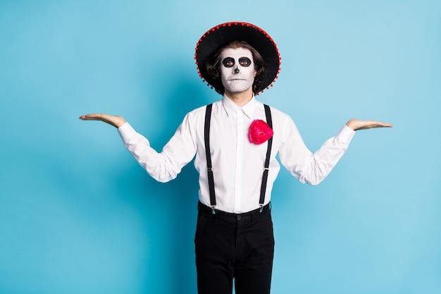 Zdjęcie zombie odgrywanie ról facet dzień śmierci nadruk twarzy makijaż trzymaj otwarte ramiona prezentując nowość dwa produkty wybierz wybór nosić kapelusz kostium szelki na białym tle niebieski kolor tła