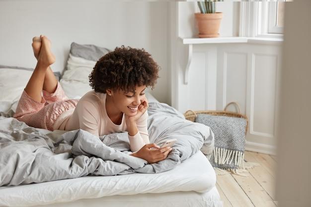 Zdjęcie zrelaksowanej ciemnoskórej kobiety oglądającej historię online na telefonie komórkowym, czyta post z ekscytującymi informacjami, ubrana w zwykłe domowe ubrania, leży na łóżku, ma radosny wyraz. przytulne wnętrze