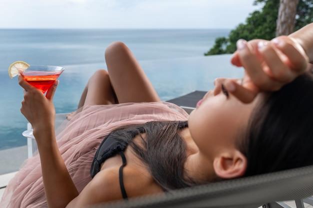 Zdjęcie zrelaksowanej kobiety leżącej przy lampce koktajlu kosmopolitycznego na tle rozmytego morza