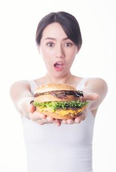 Zdjęcie zszokowana młoda kobieta azji stojącej na białym tle jedzenie burgera
