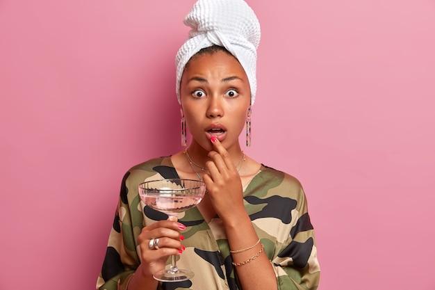 Zdjęcie zszokowanej gospodyni domowej pod wrażeniem, ma zadbaną skórę, trzyma kieliszek martini, nosi owinięty ręcznik i szlafrok khaki, odizolowany na różowej ścianie. koncepcja strony krajowej