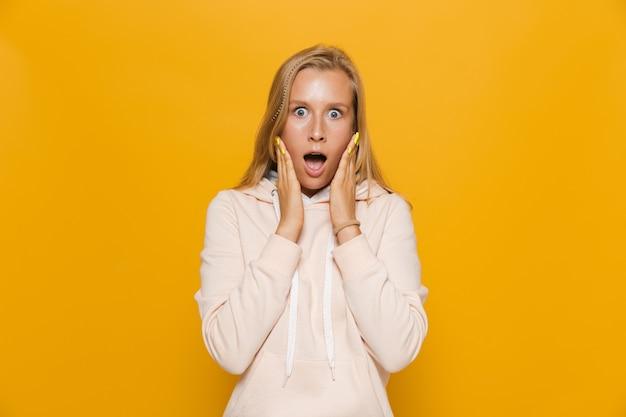 Zdjęcie zszokowanej kobiety z aparatami ortodontycznymi krzyczącej do kamery, odizolowanej na żółtym tle
