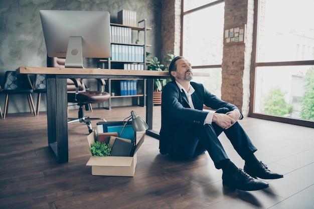 Zdjęcie zwolnionego pracownika dojrzały facet nie zwolnił agenta przegrany stracił pracę spakowany dobytek oczy zamknięte rozważania karton pudełko kryzys finansowy siedzieć podłoga parkiet myślenie plany na przyszłość biuro w pomieszczeniu