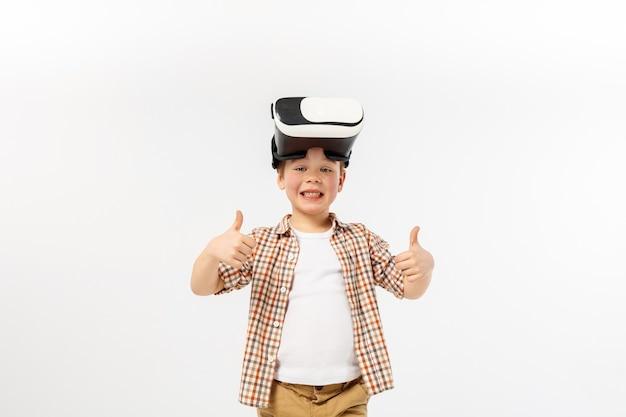 Zdobądź nowy poziom i umiejętności. mały chłopiec lub dziecko w dżinsach i koszuli z okularami zestaw słuchawkowy wirtualnej rzeczywistości na białym tle na tle białego studia. koncepcja najnowocześniejszych technologii, gier wideo, innowacji.