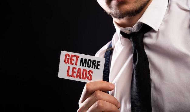 Zdobądź więcej potencjalnych klientów w męskich rękach na czarnym tle.
