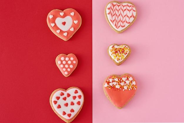Zdobione ciasteczka w kształcie serca na kolorowym czerwonym i różowym tle