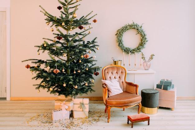 Zdobione drzewo cristmas z pudełkami, krzesłem, puchem i stołem z wiszącym na ścianie wieńcem.