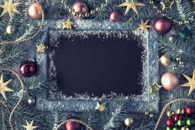Zdobione gałązki jodły wokół tablicy kredą na rustykalnym drewnie ze śniegiem. widok z góry z miejsca kopiowania.