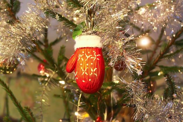 Zdobione gałęzie jodły. czerwona rękawiczka i bombka.
