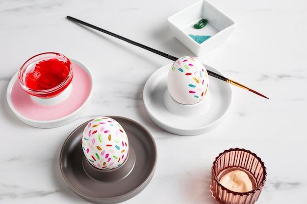 Zdobione jajko wielkanocne na talerzu z pędzlem i farbą