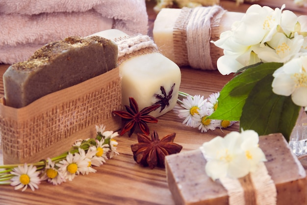 Zdobione kawałki różnych suchych mydeł z jaśminem, stokrotką, anatami i ręcznikiem