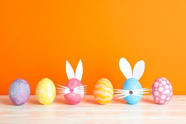 Zdobione pisanki i słodkie uszy królika na stole na kolor tła