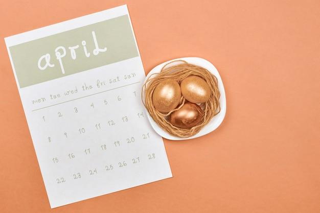 Zdobione pisanki z kalendarzem kwietniowym. jasny kalendarz miesięczny na kwiecień i złote pisanki wielkanocne