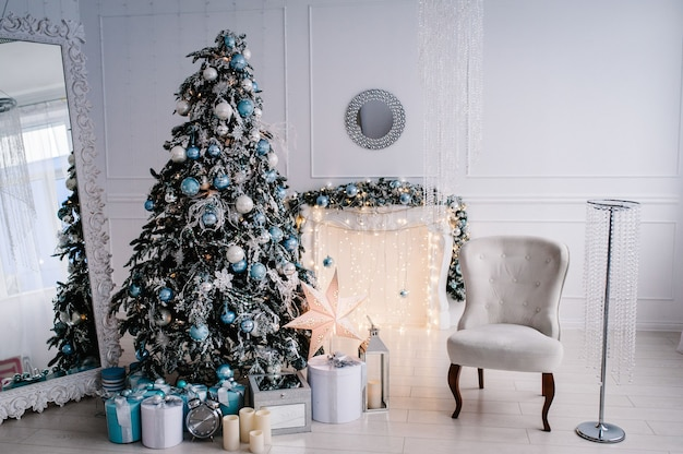 Zdobione świąteczne wnętrze. choinka z pudełka na prezenty w białym pokoju. jodła, fotel, kominek ozdobiony girlandami. dekoracje. wesołych świąt.