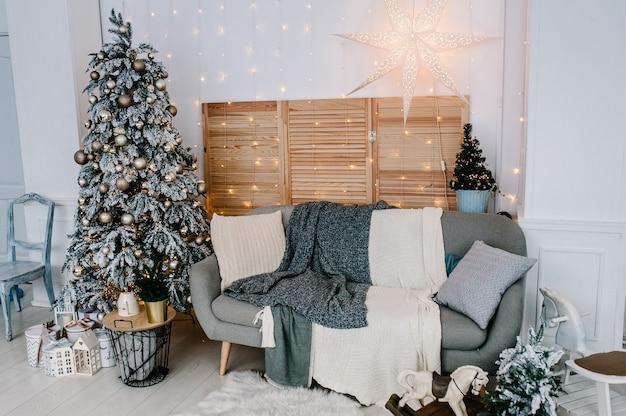 Zdobione świąteczne wnętrze. choinka z pudełka na prezenty w białym pokoju. jodła ozdobiona girlandami. dekoracje. wesołych świąt. pojęcie ferii zimowych.