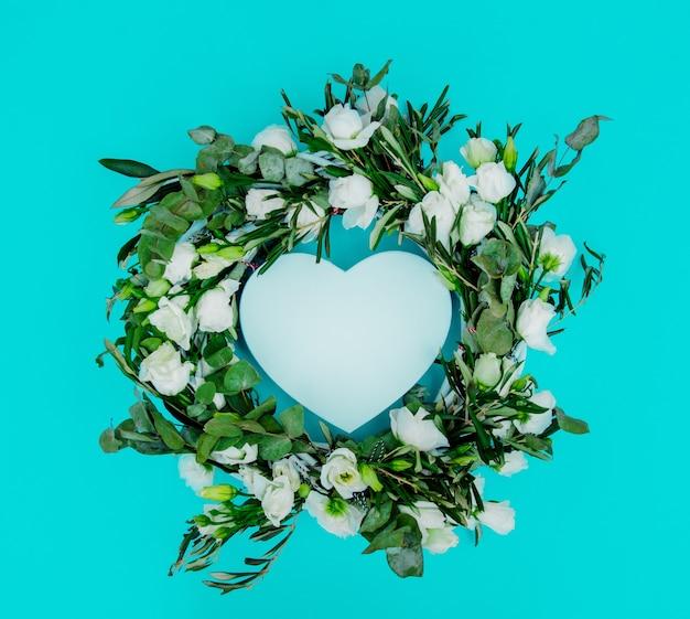 Zdobione wieniec z białych róż w kształcie serca miłość na niebieskim tle. ozdobiony. powyżej widok