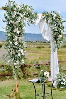 Zdobiony łuk ślubny z zielenią i białymi eustomami w ogrodach na zewnątrz