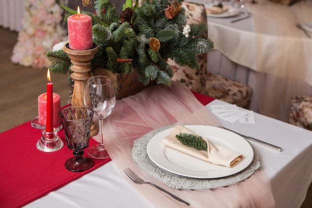 Zdobiony stół ze świecami i gałązkami jodły. dekoracja świąteczna kolacja.