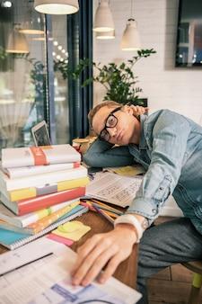 Zdobywanie wiedzy. poważny młody student siedzący przy stole w otoczeniu książek