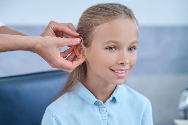 Zdolność słyszenia. śliczna uśmiechnięta dziewczyna z długimi włosami i opiekuńczymi rękami otolaryngologa z aparatem słuchowym w pobliżu ucha