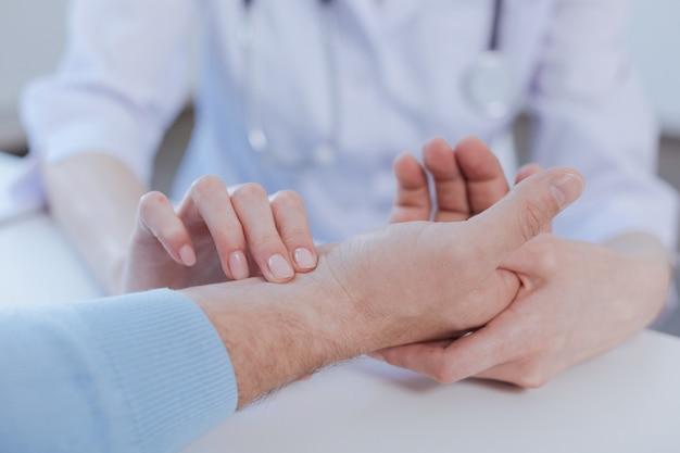 Zdolny, dojrzały, profesjonalny lekarz cieszący się wizytą i mierzący tętno pacjenta, stosując umiejętności zawodowe