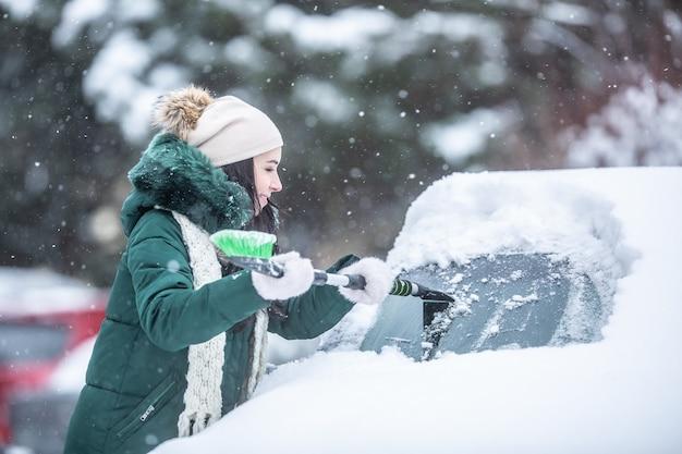 Zdrapywanie lodu z samochodu po obfitych opadach śniegu pokryło go zaparkowanym na zewnątrz.
