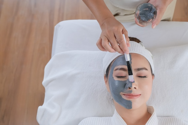 Zdrój kobieta stosuje glinianą twarzową maskę. zabieg upiększający.