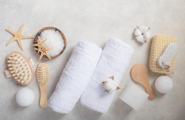 Zdroju piękna kosmetyczni produkty i narzędzia na bielu betonują tło. widok z góry