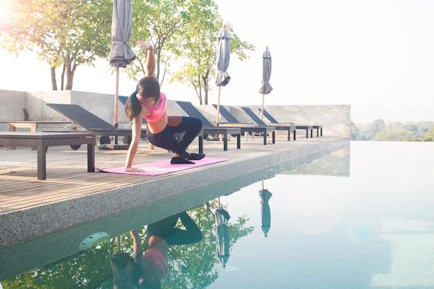 Zdrowa azjatykcia kobieta robi joga i ćwiczy blisko pływackiego basenu. zdrowe i dobre samopoczucie