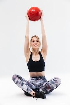 Zdrowa blond kobieta w wieku 20 lat ubrana w odzież sportową, ćwicząca i wykonująca ćwiczenia z piłką fitness podczas aerobiku na białym tle nad białą ścianą
