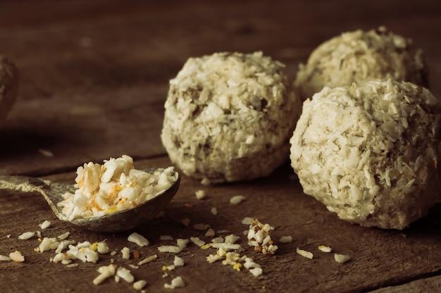 Zdrowa czekolada gryzie orzechy, daktyle, płatki kokosowe na drewnianym stole. domowe wegetariańskie bezglutenowe zdrowe przekąski. tonowanie w stylu rustykalnym.