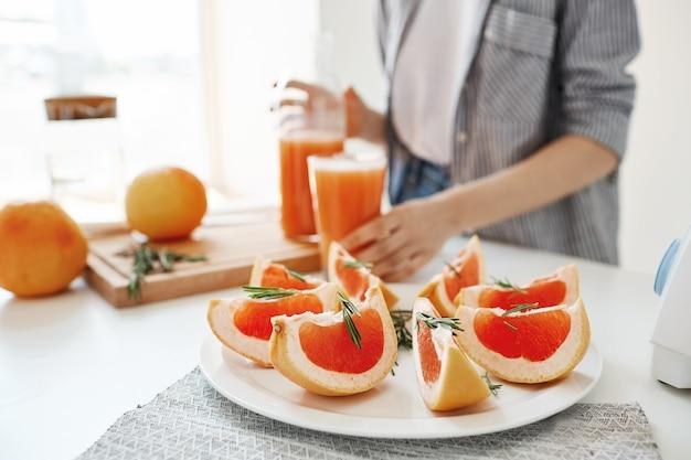 Zdrowa dieta fitness śniadanie. odświeżający koktajl detoksykacyjny. skoncentruj się na plasterkach grejpfruta. dziewczyna w tle.