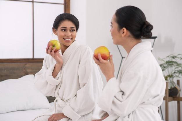 Zdrowa dieta. pozytywne ładne atrakcyjne kobiety wydrążające jabłka, patrząc na siebie