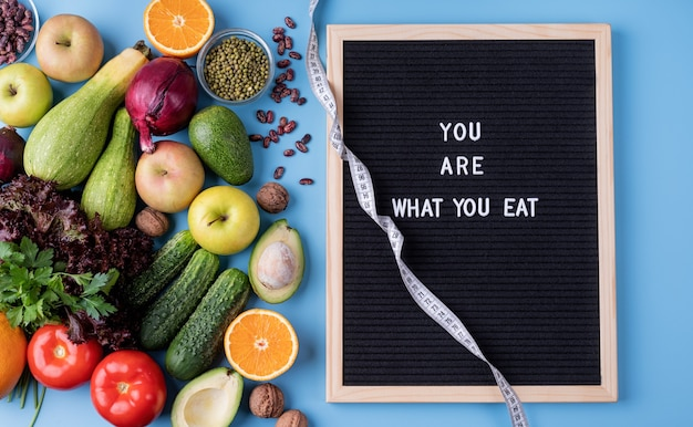 Zdrowa dieta. świeże warzywa i owoce dla zdrowej diety, miarka i czarna tablica z literami