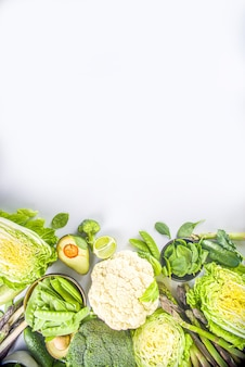 Zdrowa dieta wiosna żywności tło. asortyment świeżych surowych ekologicznych zielonych warzyw - brokuły, kalafior, cukinia, ogórki, szparagi, szpinak, awokado, kapusta na białym tle