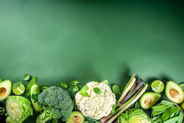 Zdrowa dieta wiosna żywności tło. asortyment świeżych surowych ekologicznych zielonych warzyw - brokuły, kalafior, cukinia, ogórki, szparagi, szpinak, awokado, kapusta na ciemnozielonym tle